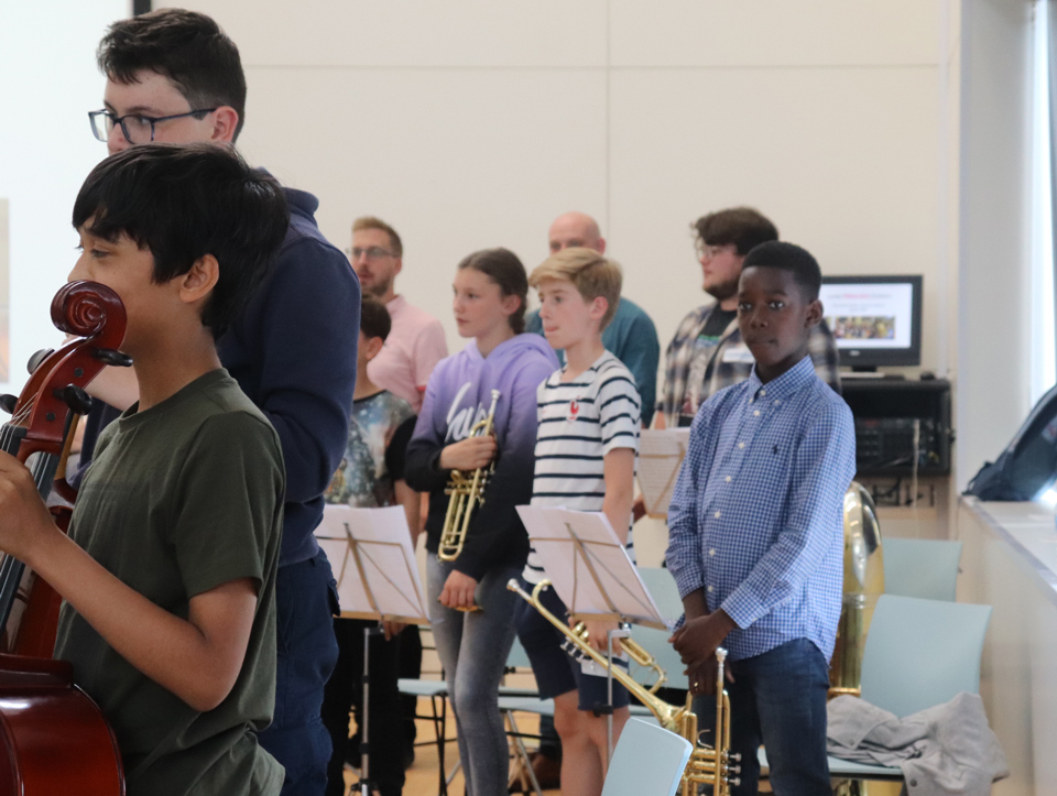 Group of teenagers at an orchestral rehearsal with London Philharmonic Orchestra