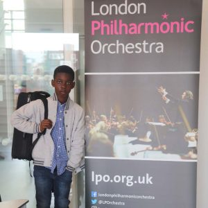 boy standing next to banner for London Philharmonic Orchestra