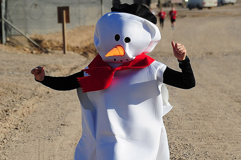 Person running in a race in a snowman costume