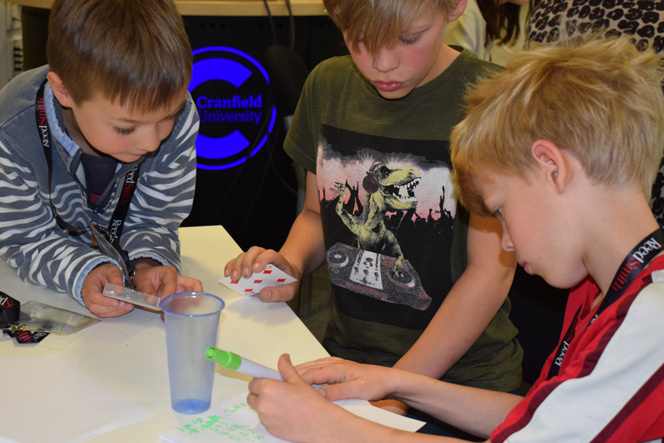 three boys around a table taking part in an activity