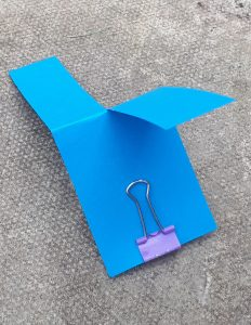 A paper helicopter with a bulldog clip weight