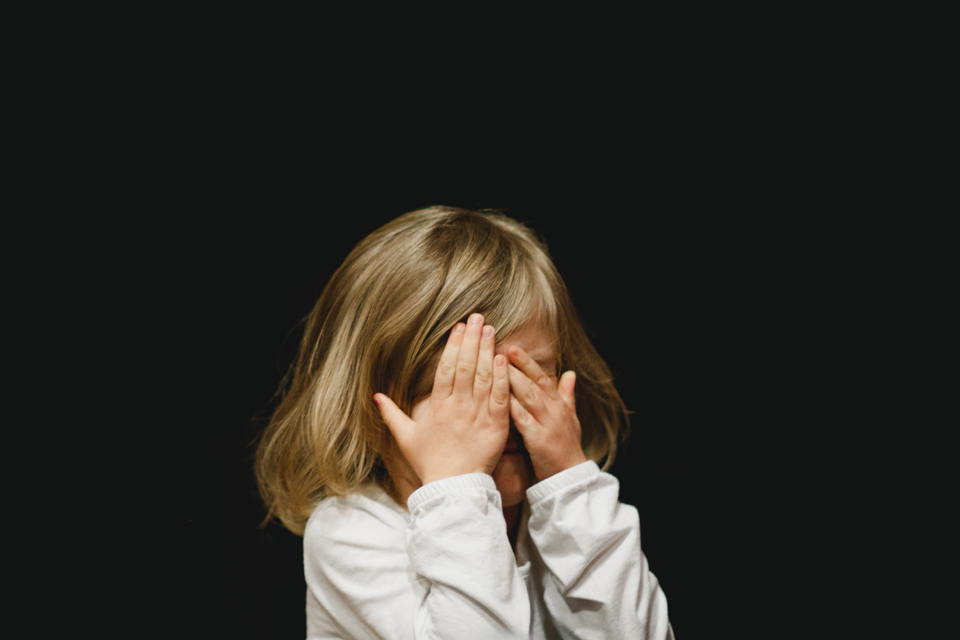young girl with hands over face