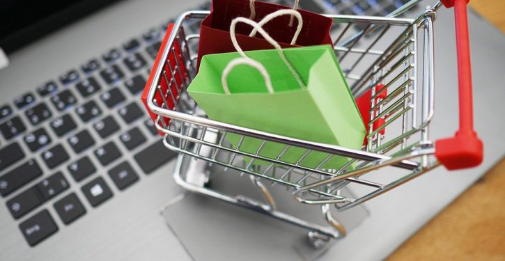 mini shopping cart with bags sitting on a computer keyboard