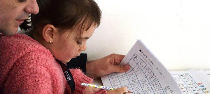 father helping his very young daughter with japanese writing
