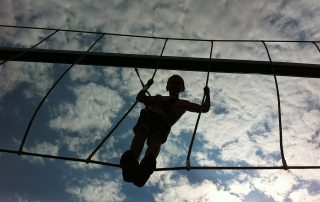 Boy silhouetted against the sky on a highwire