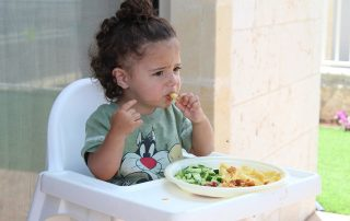 Child in a high chair not sure whether she is happy eating or not
