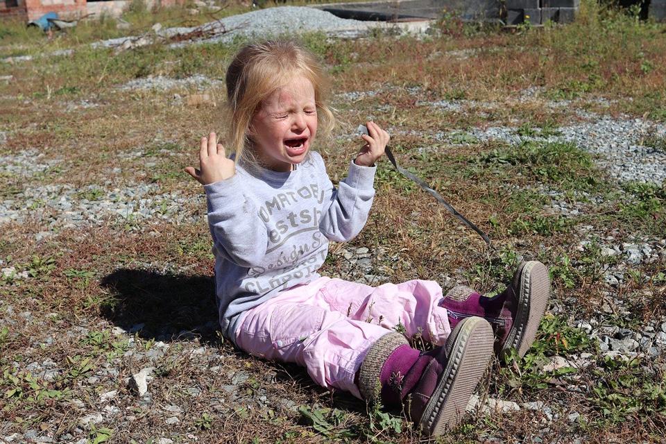 child sitting on the ground having a meltdown