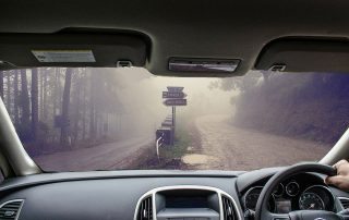 Looking through the dashboard of a car and seeing a misty road with choice of routes