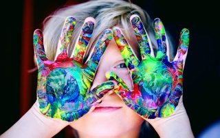 Child holding hands up in front of face. Hands are covered in rainbow paint