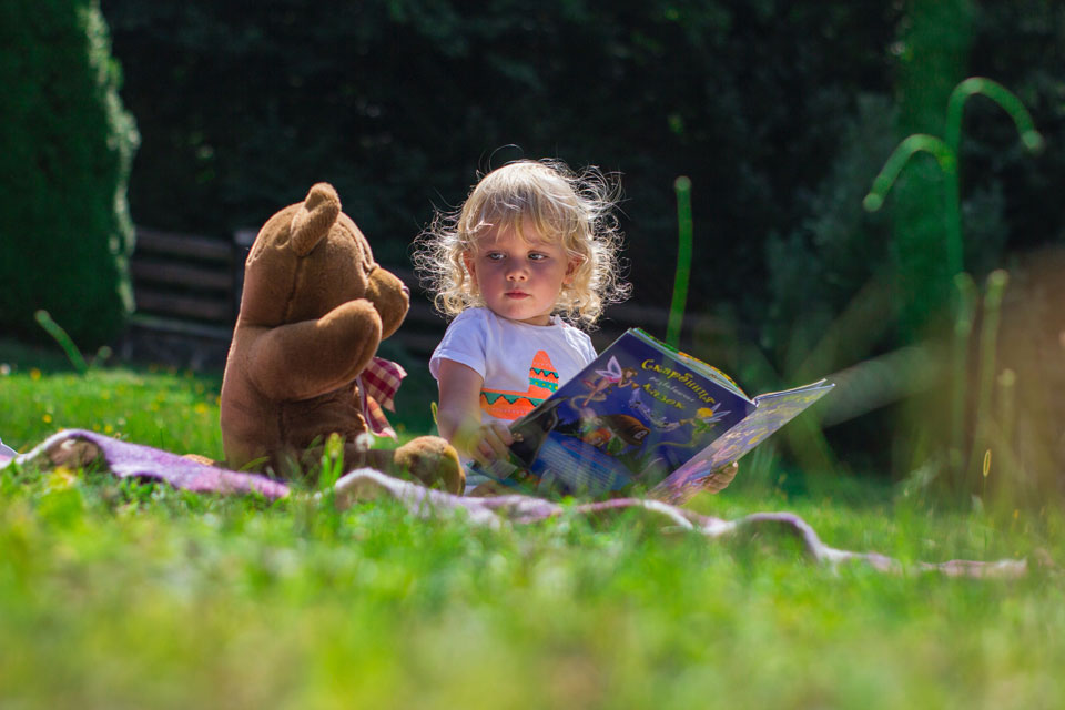 Young girl reading book to a teddy bear while sitting on the grass in the sunshine