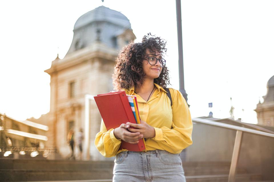 female student holding a folder standing outside university