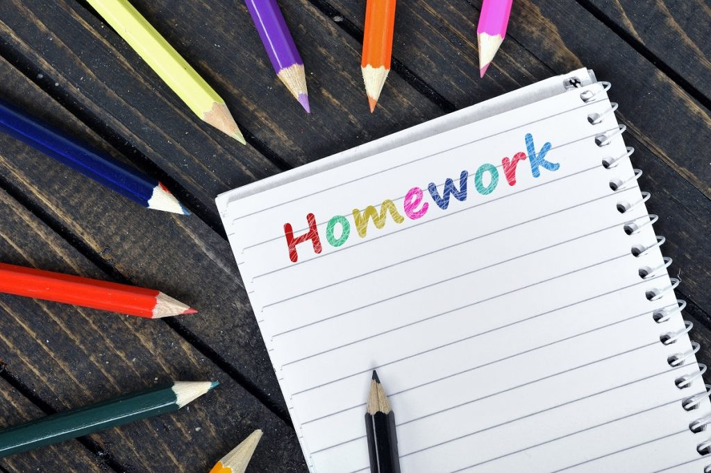 Pad with the word homework in coloured letters, coloured pencils surround the pad, with pencil points facing towards the pad