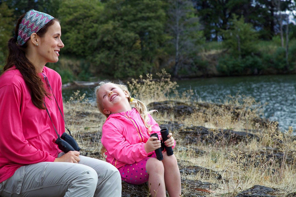 Mother and happy child outdoors with binoculars