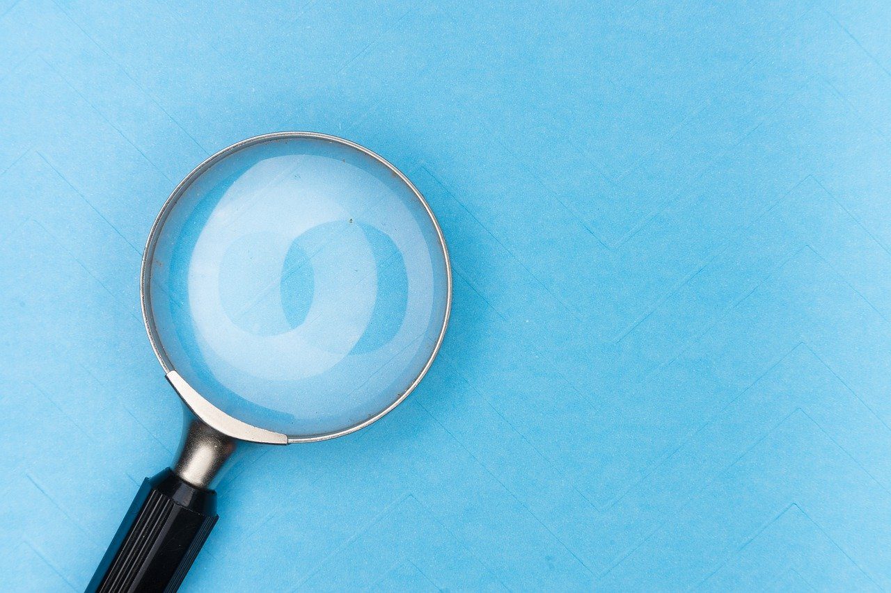Magnifying glass looking at a blue background with the effect as though the magnifier is seeing paint