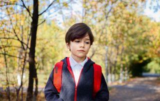 Sad schoolboy standing in a park