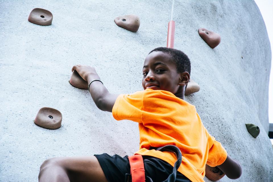 Boy half way up a climbing wall looking back at the camera and smiling