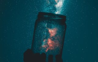 Appearing to catch a galaxy of stars in a glass jar