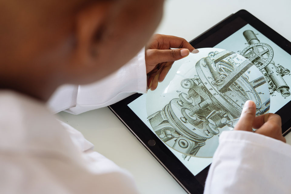 Young person looking at the structure of a mediaeval telescope on an ipad