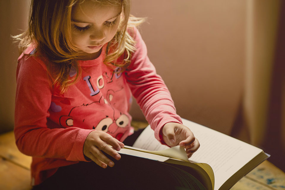 Toddler sitting reading a book
