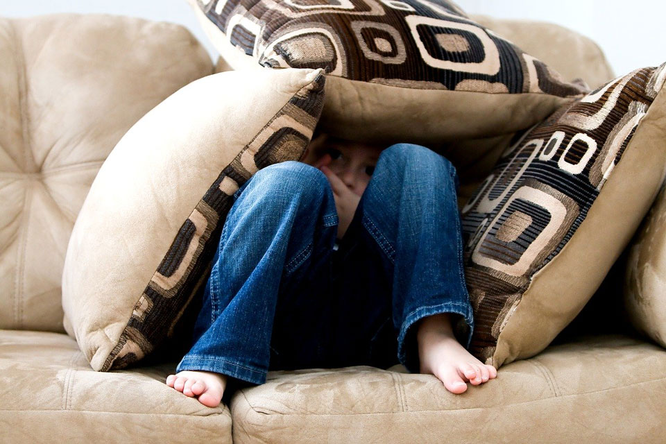 Boy hiding in cushions on the sofa