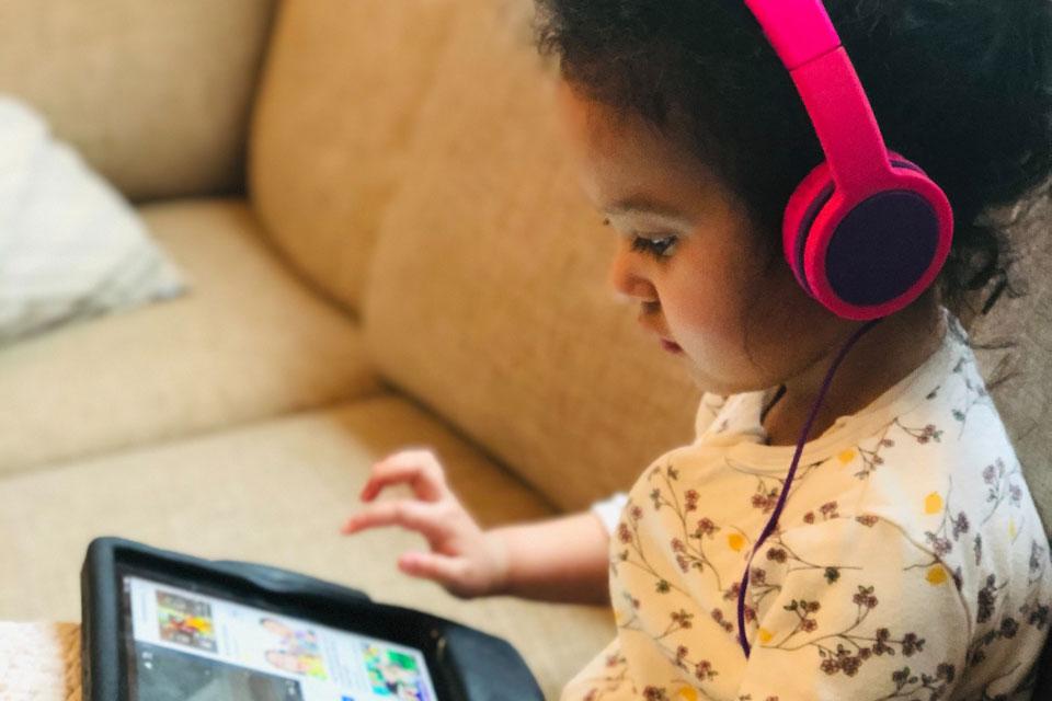 Girl in headphones looking at an ipad