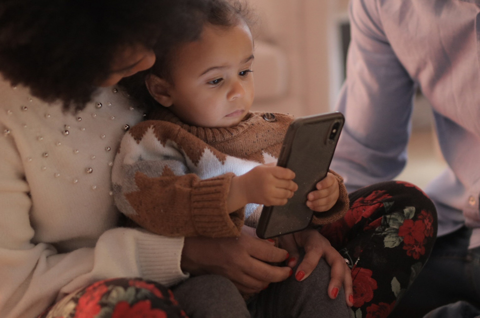 Toddler reading a mobile phone