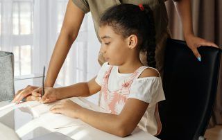 Child writing homework with mother standing next to her to help