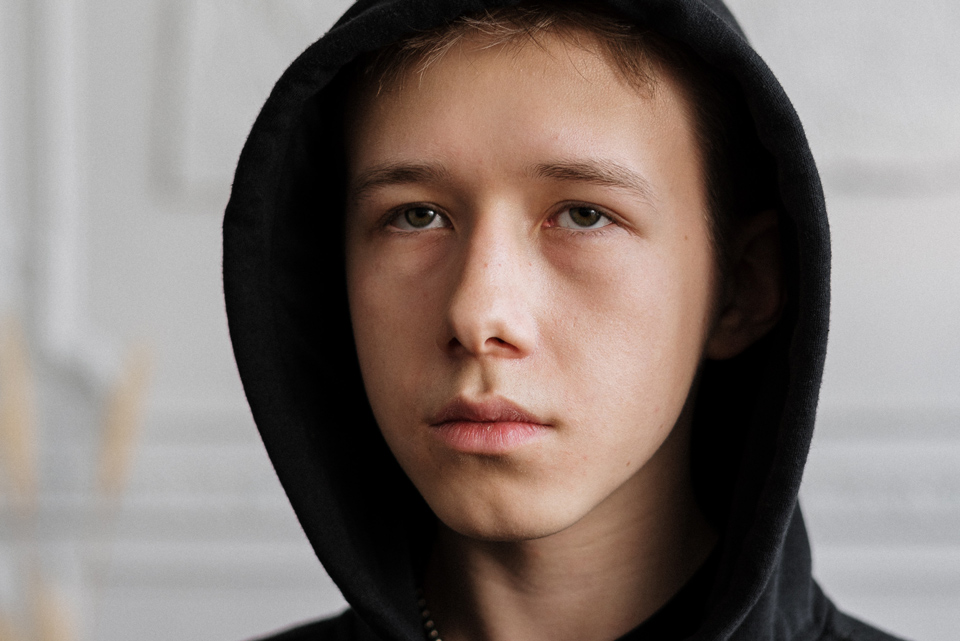Boy wearning a hoodie looking into the distance with a solemn expression
