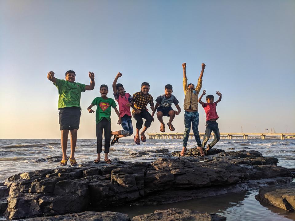 Group of Children on the seashore jumping for joy