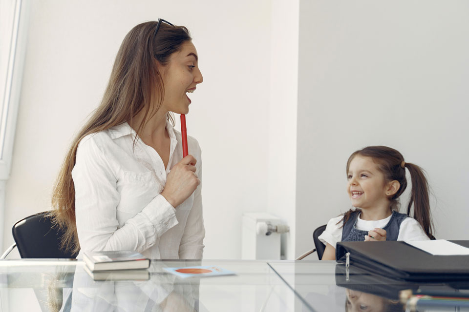Woman and young child at a table laughing