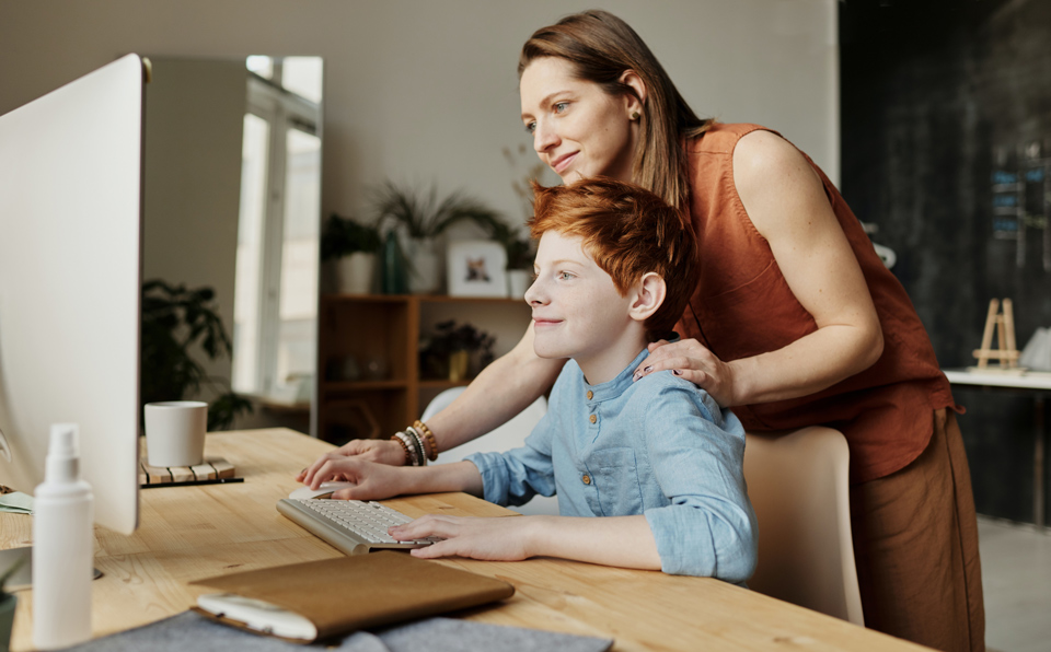 Photo of woman teaching her son while smiling