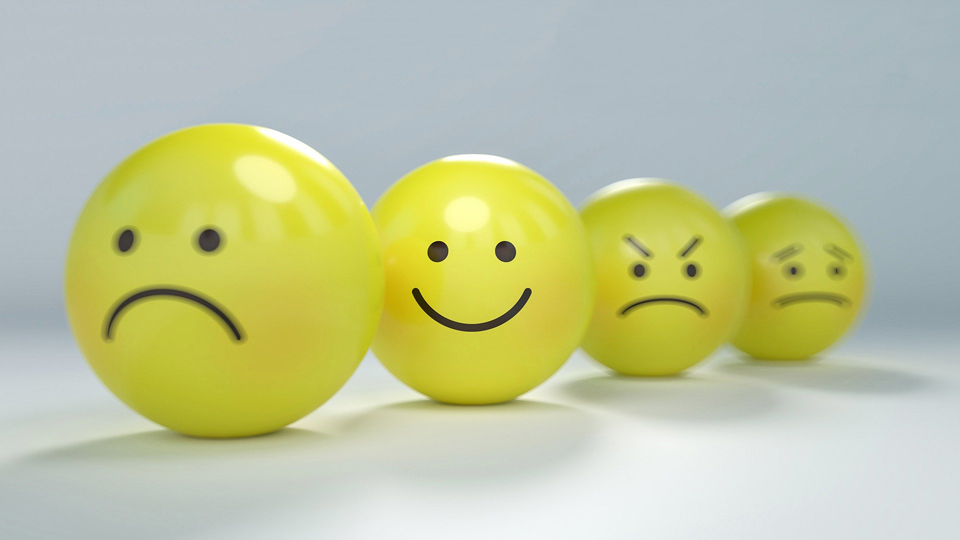 Yellow rubber balls with smiley emoticon faces, emphasis on the happy smiley face
