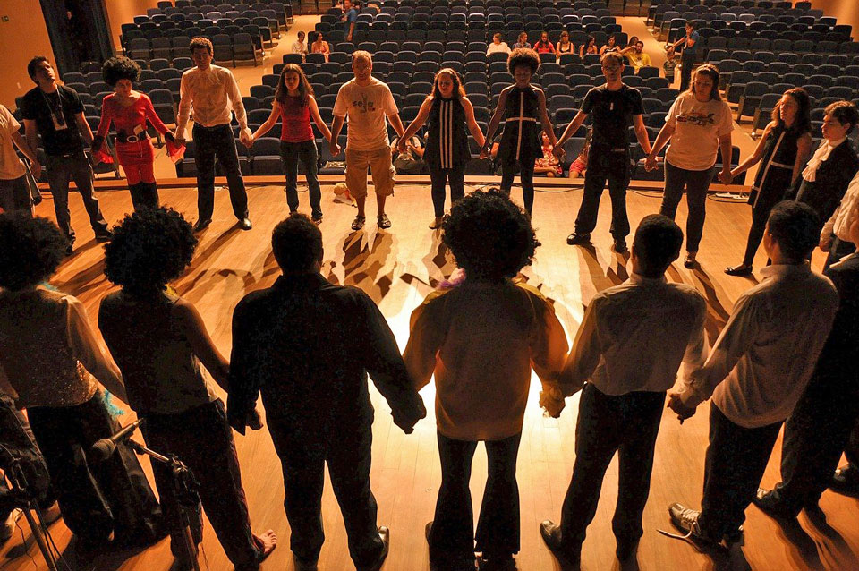 Group of teenagers standing on a stage in a circle holding hands