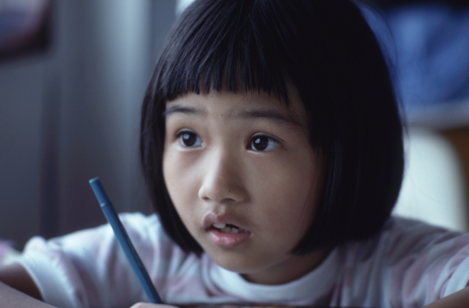 Young child holding a pen