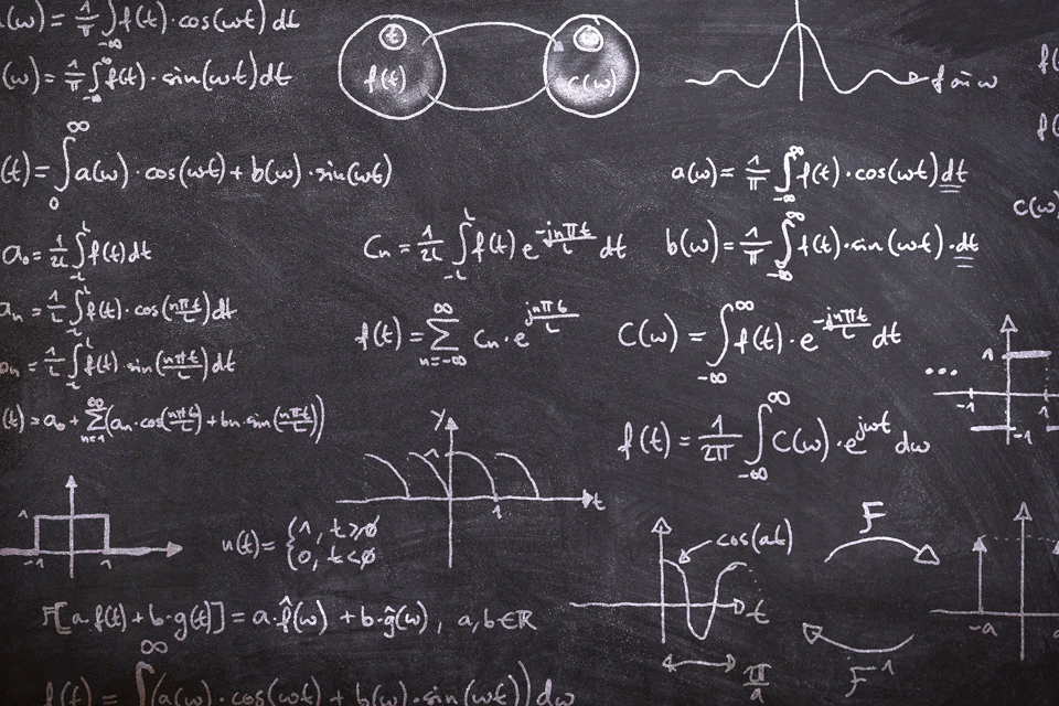 Photo of a blackboard full of complicated maths formulas