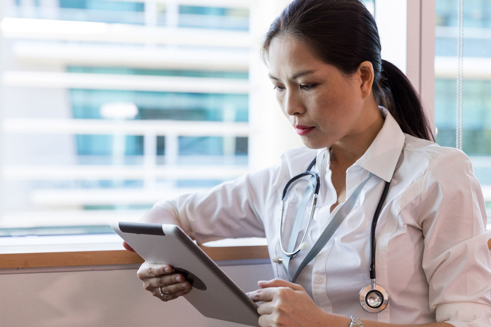 Photo of a female doctor studying a tablet computer