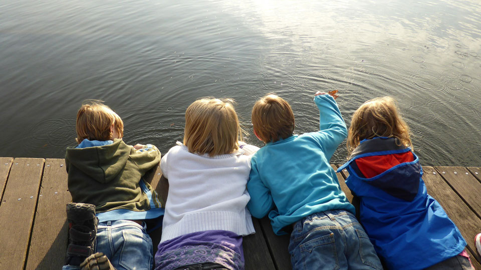 4 girls and boys lying prone on a jetty looking into the water
