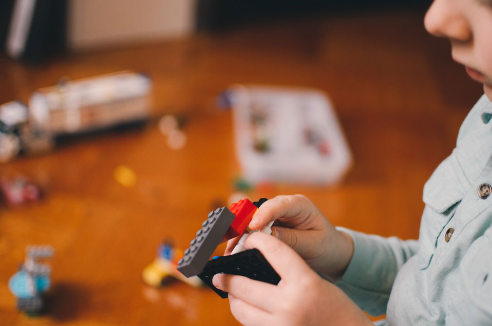 Young child building with lego