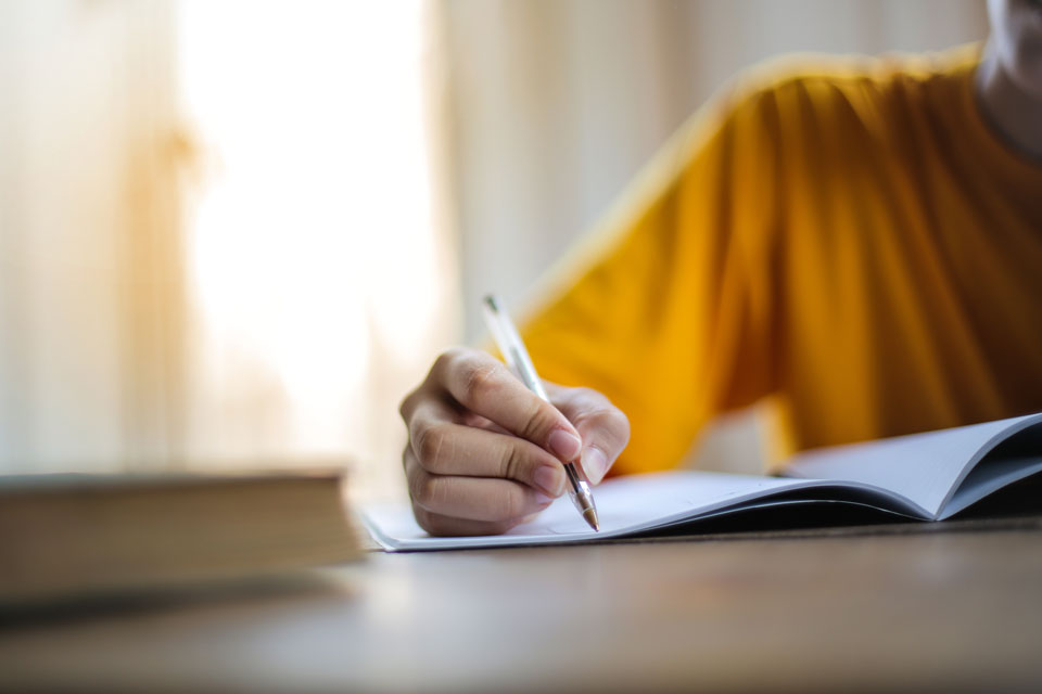 Hand of an adult holding a pen writing in a booklet