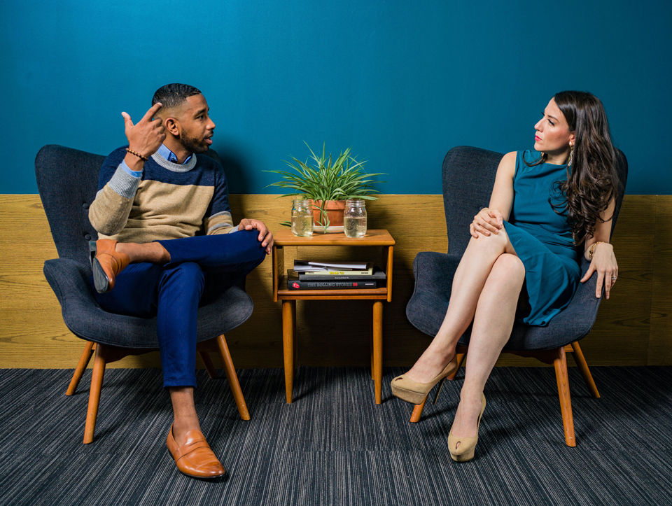Man talking in an animated fashion to a woman who is listening intently