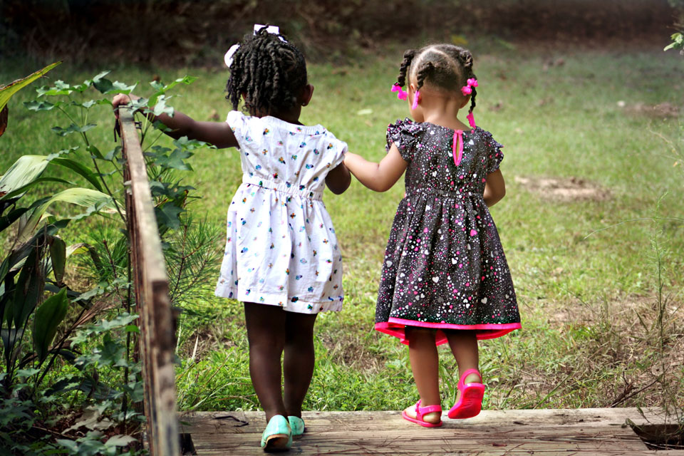 Two very young girls walking hand in hand over a bridge