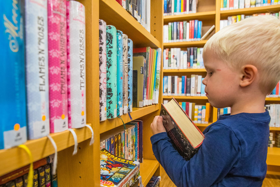 young child in a library looking at advanced books