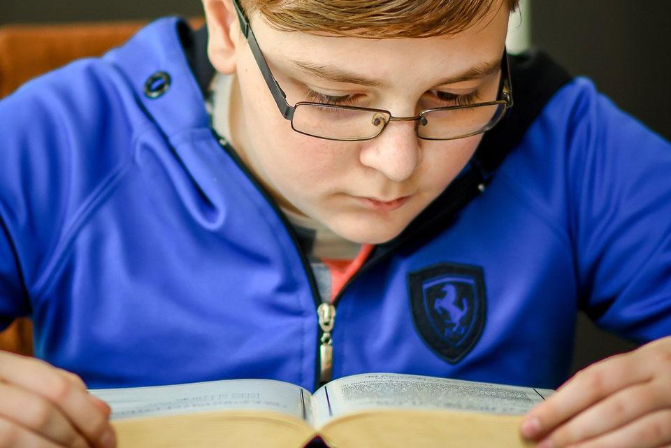 teenage boy studying a book
