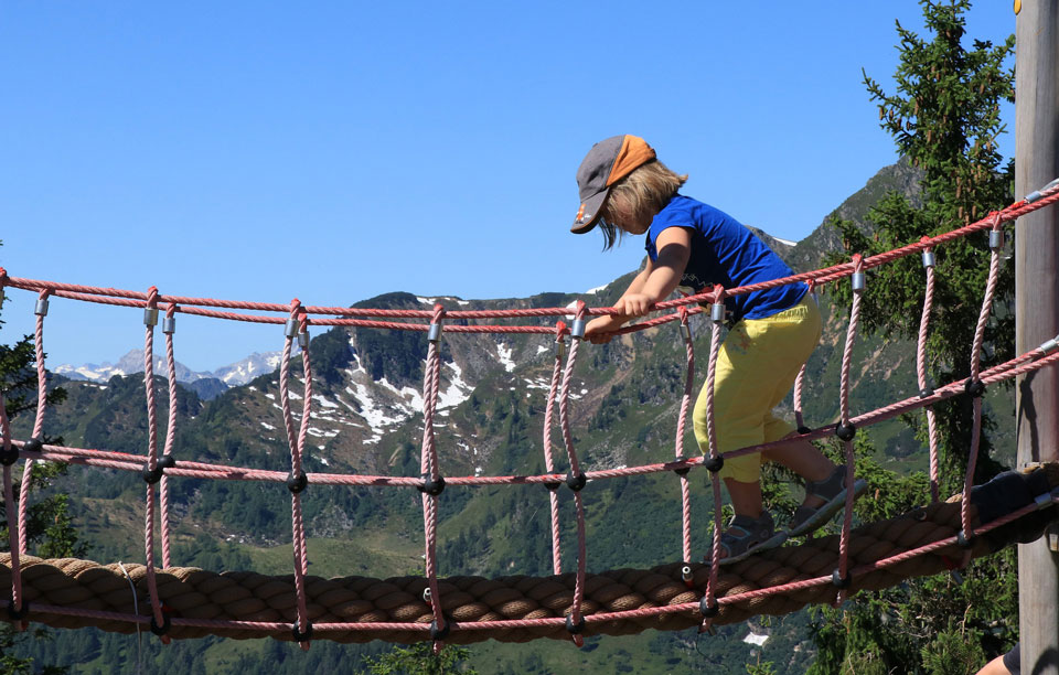 Young child confidently crossing a rope bridge