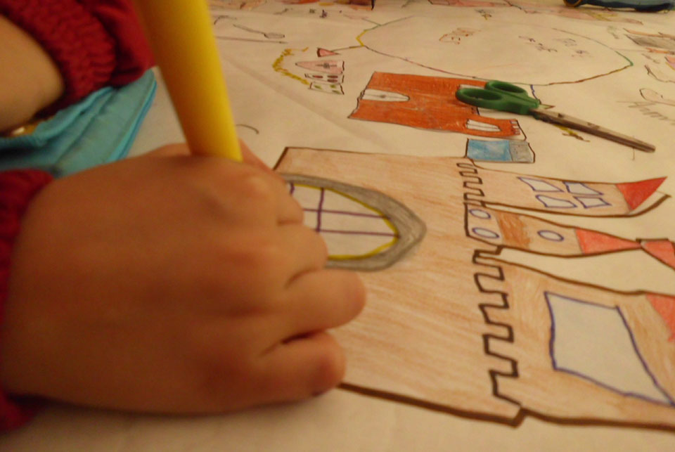young child drawing a castle