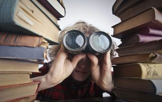 person staring through binoculars surrounded by piles of books