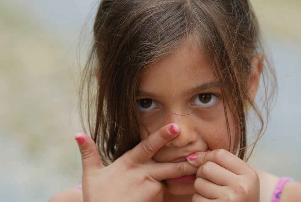 young girl biting her fingers