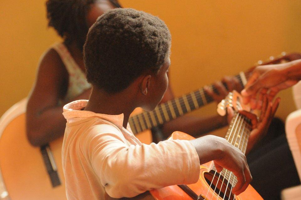 two primary school aged children learning to play guitar