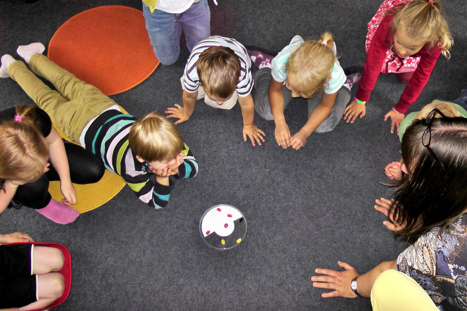 group of nursery age children gathered in a circle facing a dish with some sweets in it