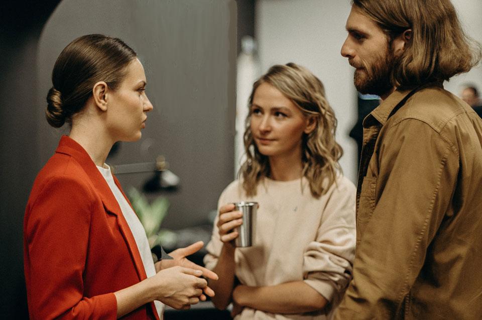 three adults standing talking